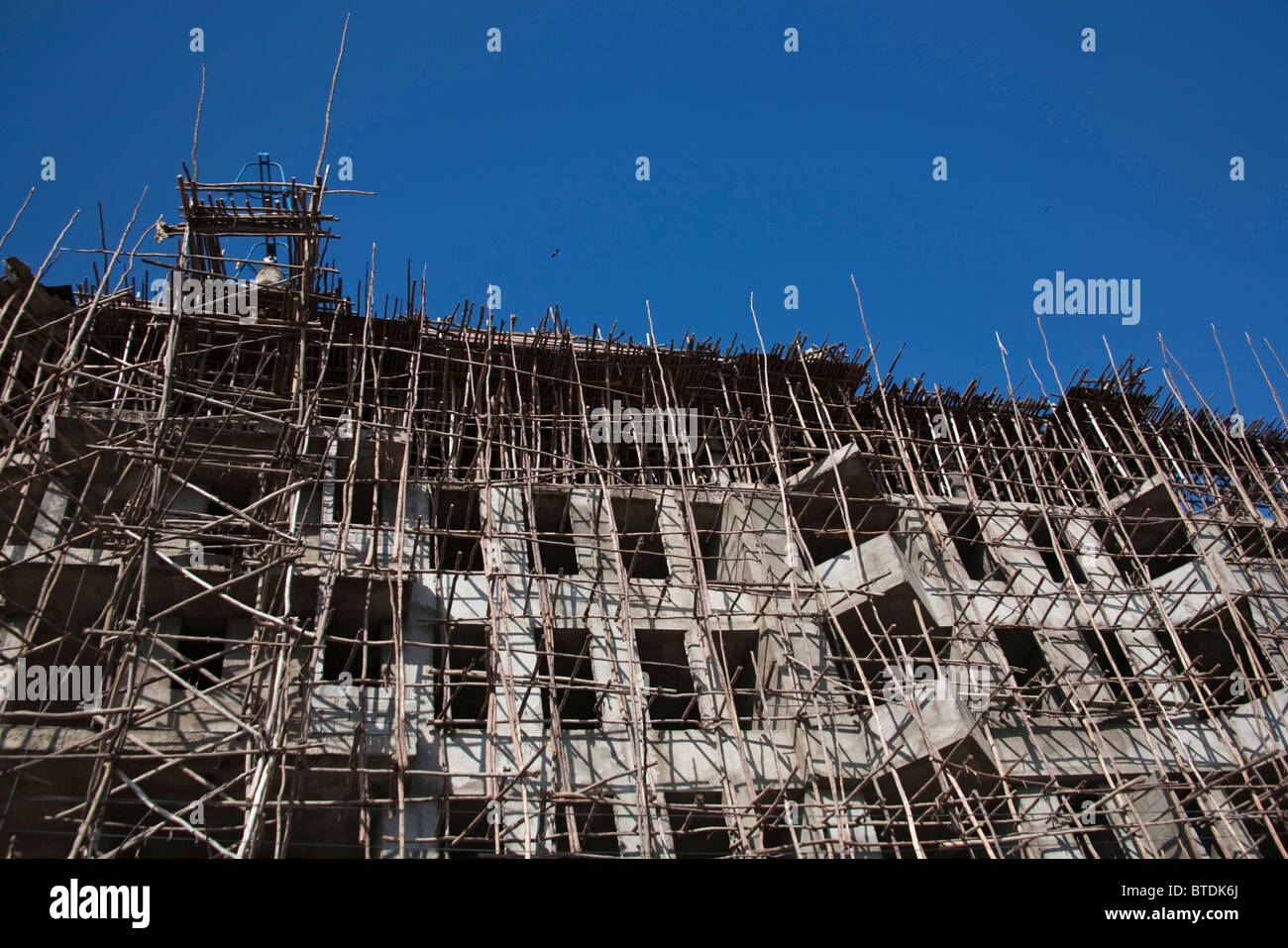 Construction and wooden scaffolding and screens in downtown Awassa on a multi-story building - Stock Image