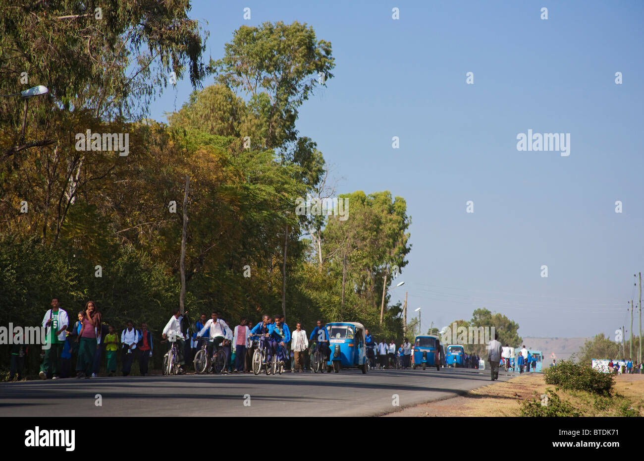 Scholars, pedestrians and bajaj taxis walking into Awassa - Stock Image