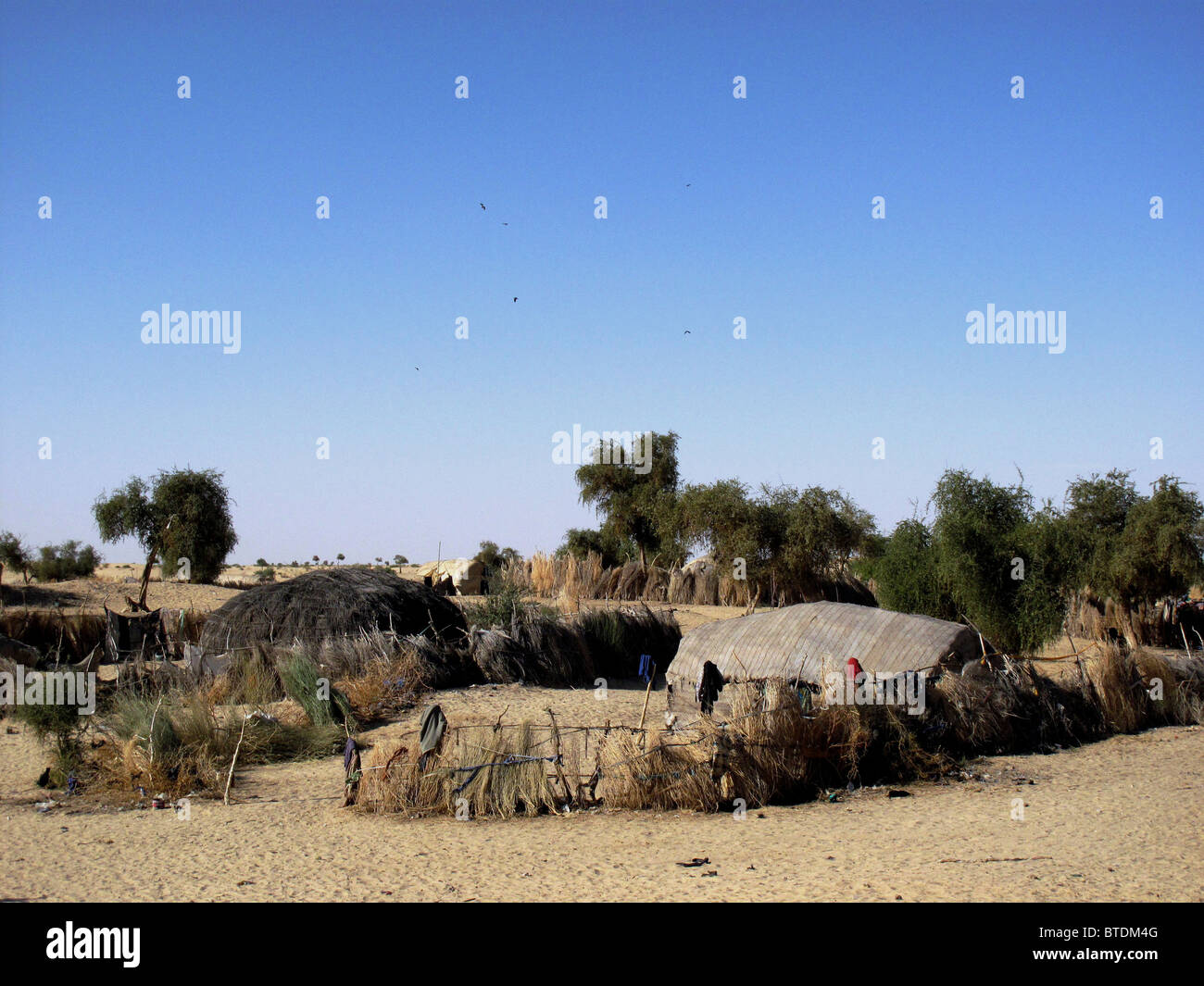 A rural village with huts and fences made of thatch - Stock Image