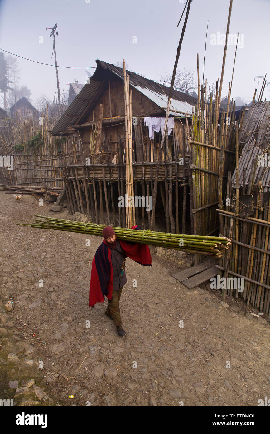 An Apatani tribal man walks through the rows of bamboo huts on stilts in the village of Hijja, Arunachal Pradesh. - Stock Image