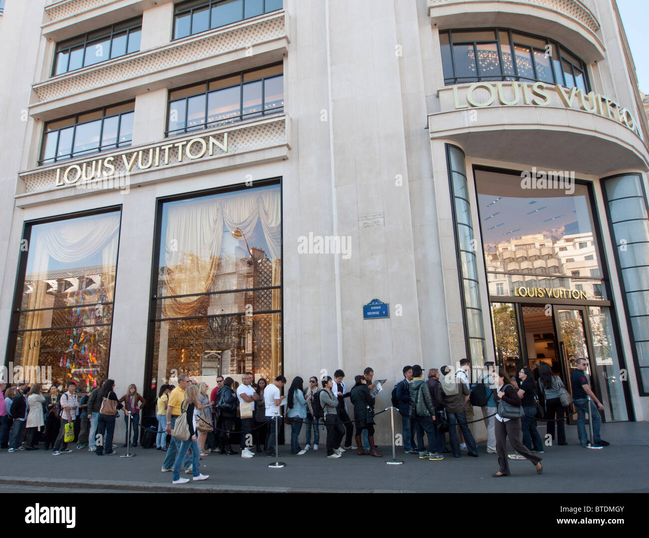 Queue of shoppers outside Louis Vuitton store on Champs Elysees in Paris France - Stock Image