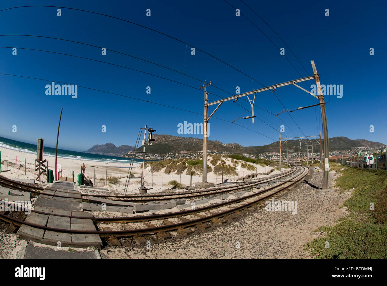 Fish-eye view of railway tracks running past Fish Hoek beach and a view of Table mountain in the background - Stock Image