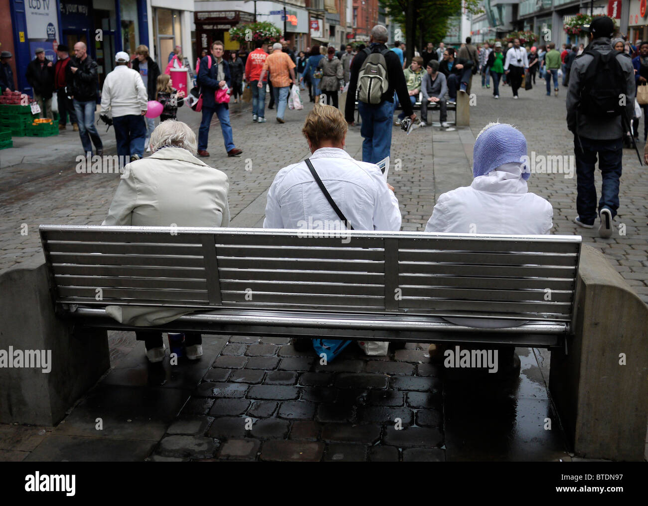 Three ladies seated on Market Street in Manchester City Centre UK - Stock Image