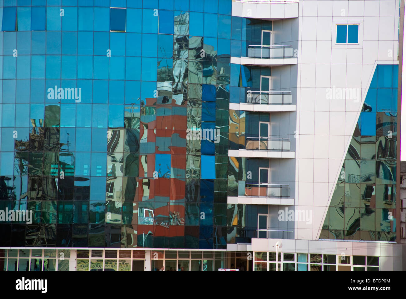 Reflections in the blue glass frontage of a modern building in downtown Addis Ababa - Stock Image