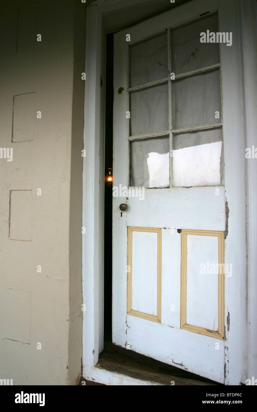 An old white wooden door left slightly ajar with the faint light from a paraffin lamp just visible - Stock Image