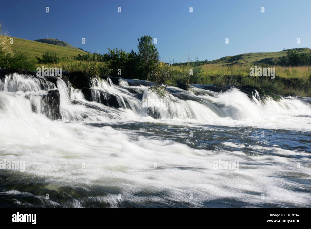 A river flowing swiftly over rocks - Stock Image