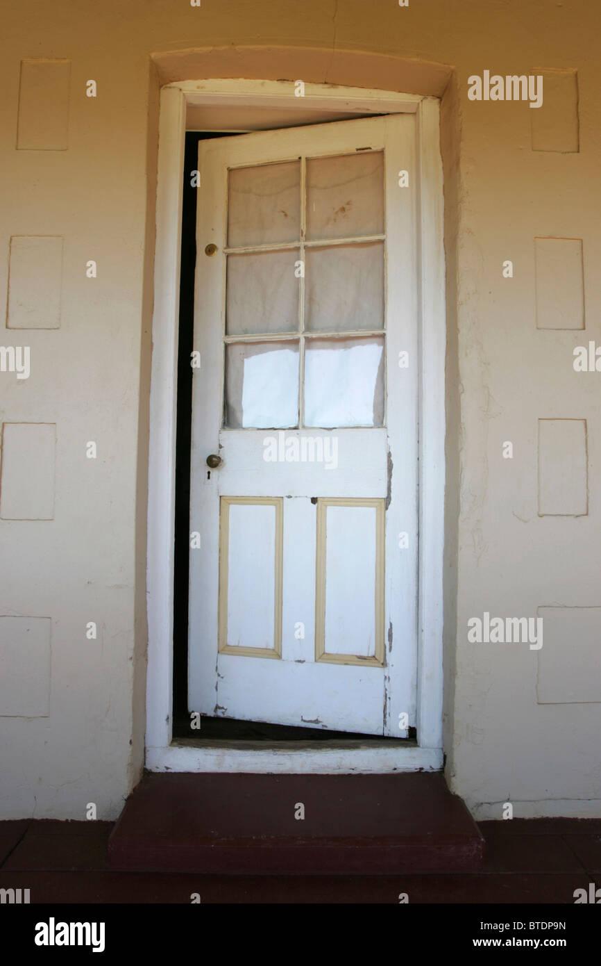 A wooden and glass door standing slightly ajar - Stock Image
