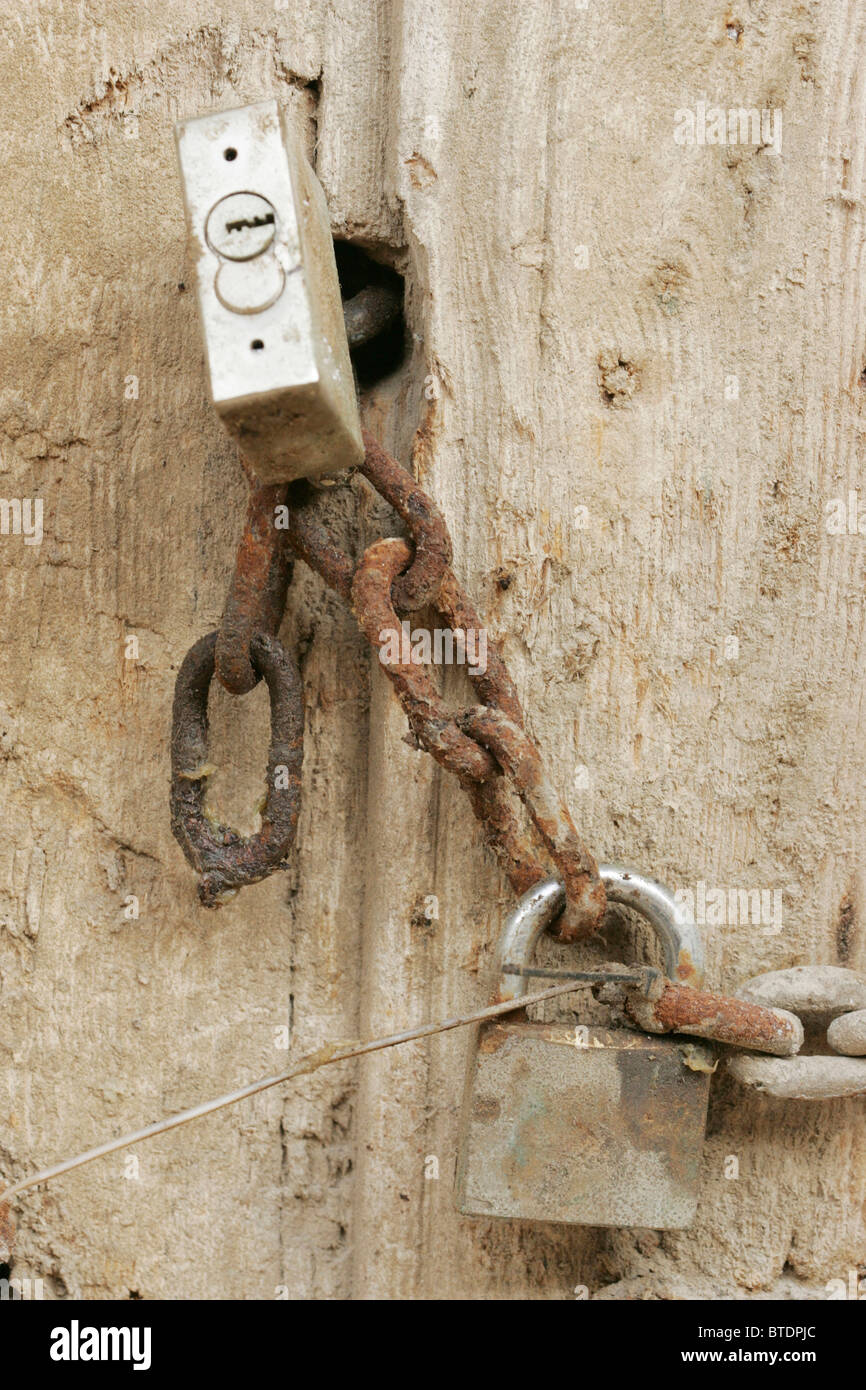 Padlocks on a rusted chain - Stock Image