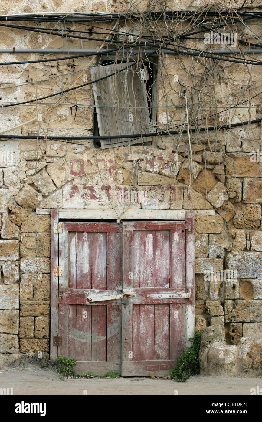Wooden Doors With Hebrew Writing Above The Door Jamb And A Board Covering A  Loft Window