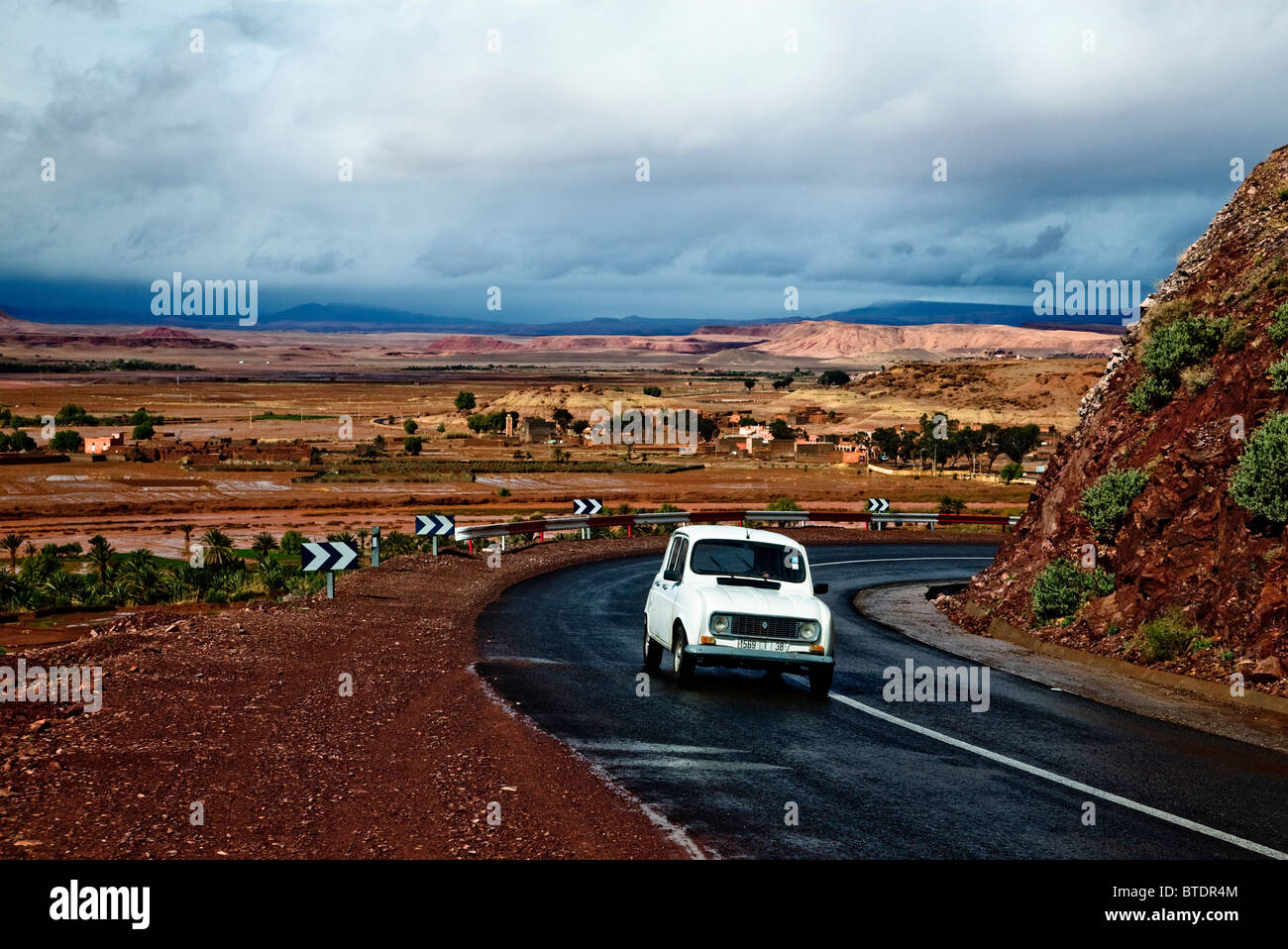 Old car on a narrow winding tar road with storm clouds over a plain - Stock Image