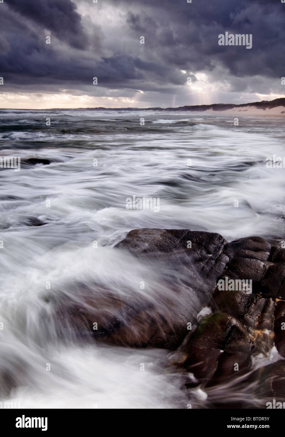 Moody seascape with rocks in the foreground and lighting over the sea - Stock Image