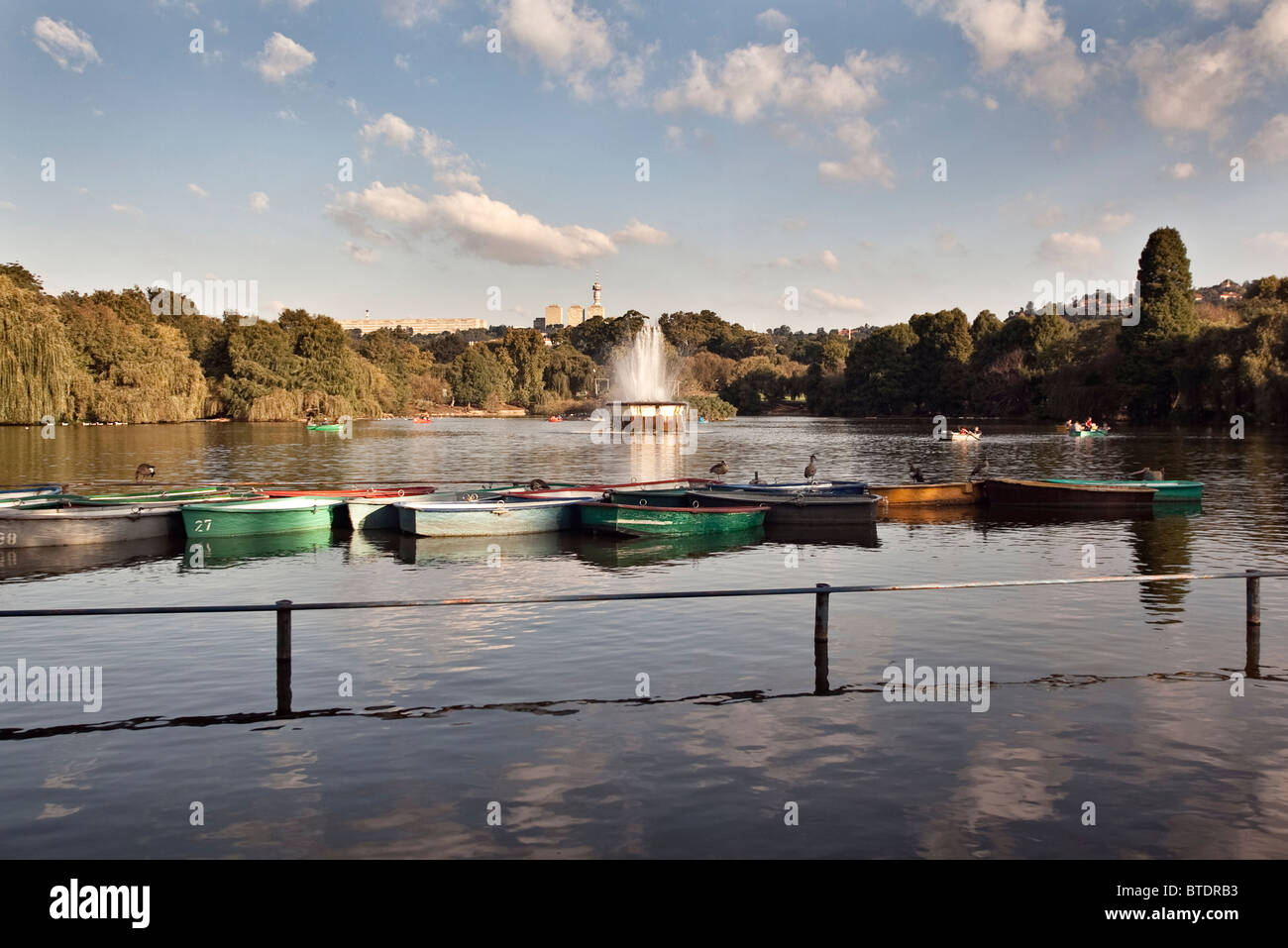 Rowing boats at Zoo Lake with a fountain in the background - Stock Image