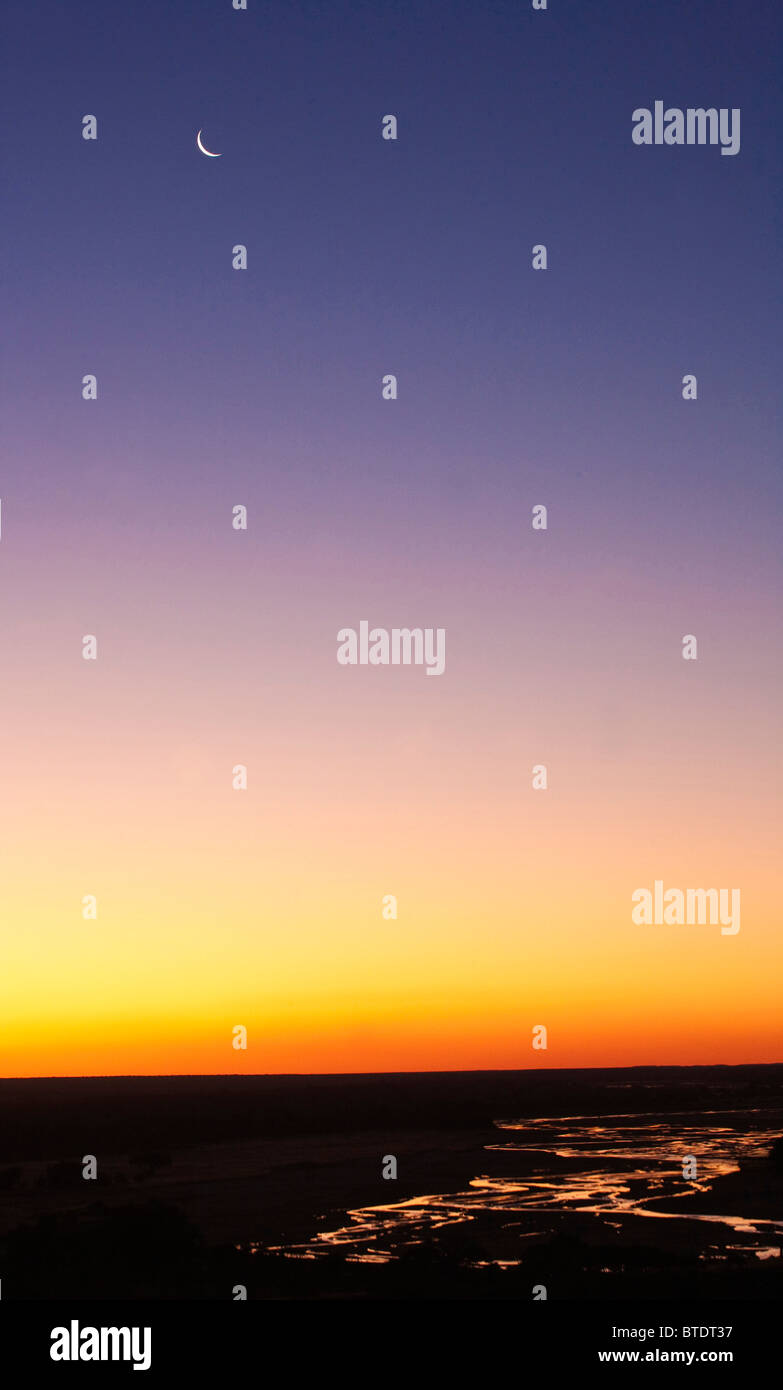 Scenic landscape of the Shashe River at dusk with a sickle moon - Stock Image