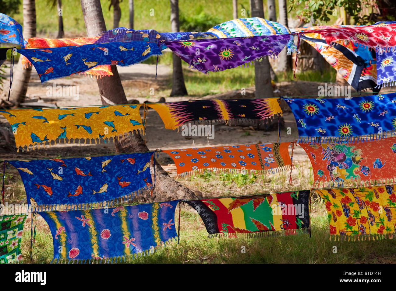 Colourful printed cloths for sale at a roadside stall - Stock Image