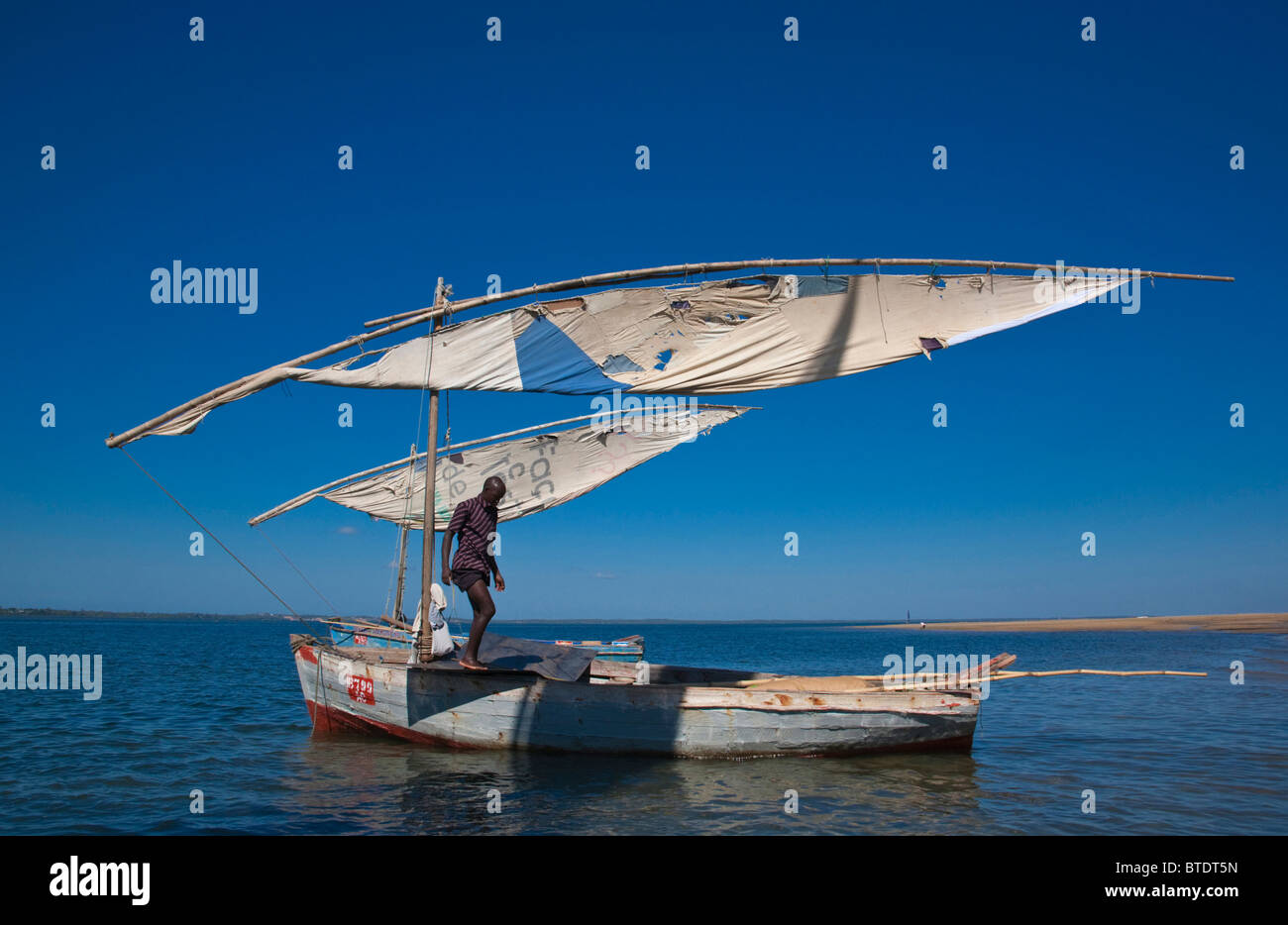 A dhow or traditional sailing boat sailing on a blue sea - Stock Image