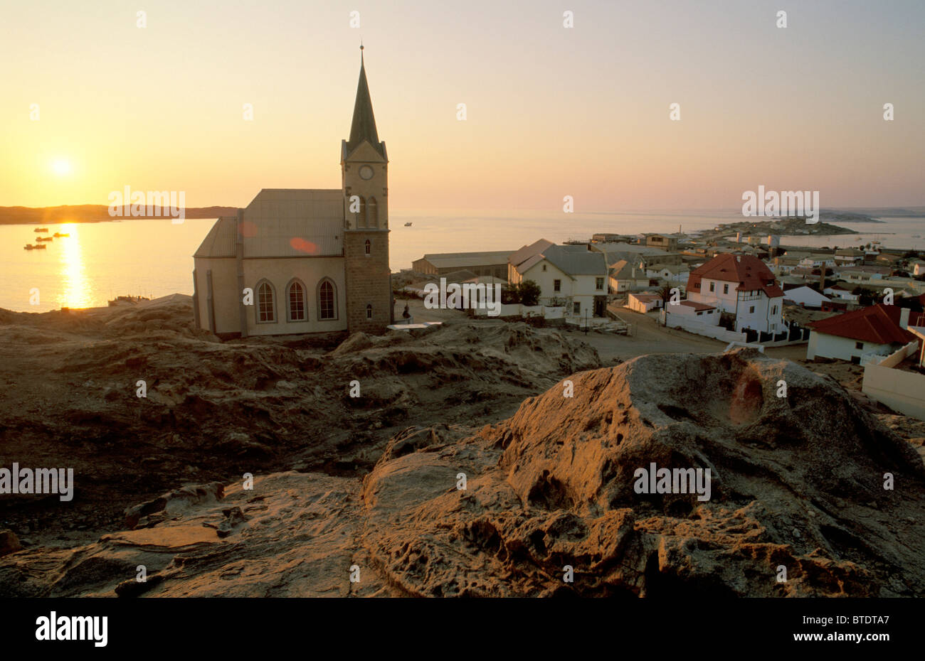 The German Lutheran church and the town of Luderitz with the sun setting over the harbour - Stock Image