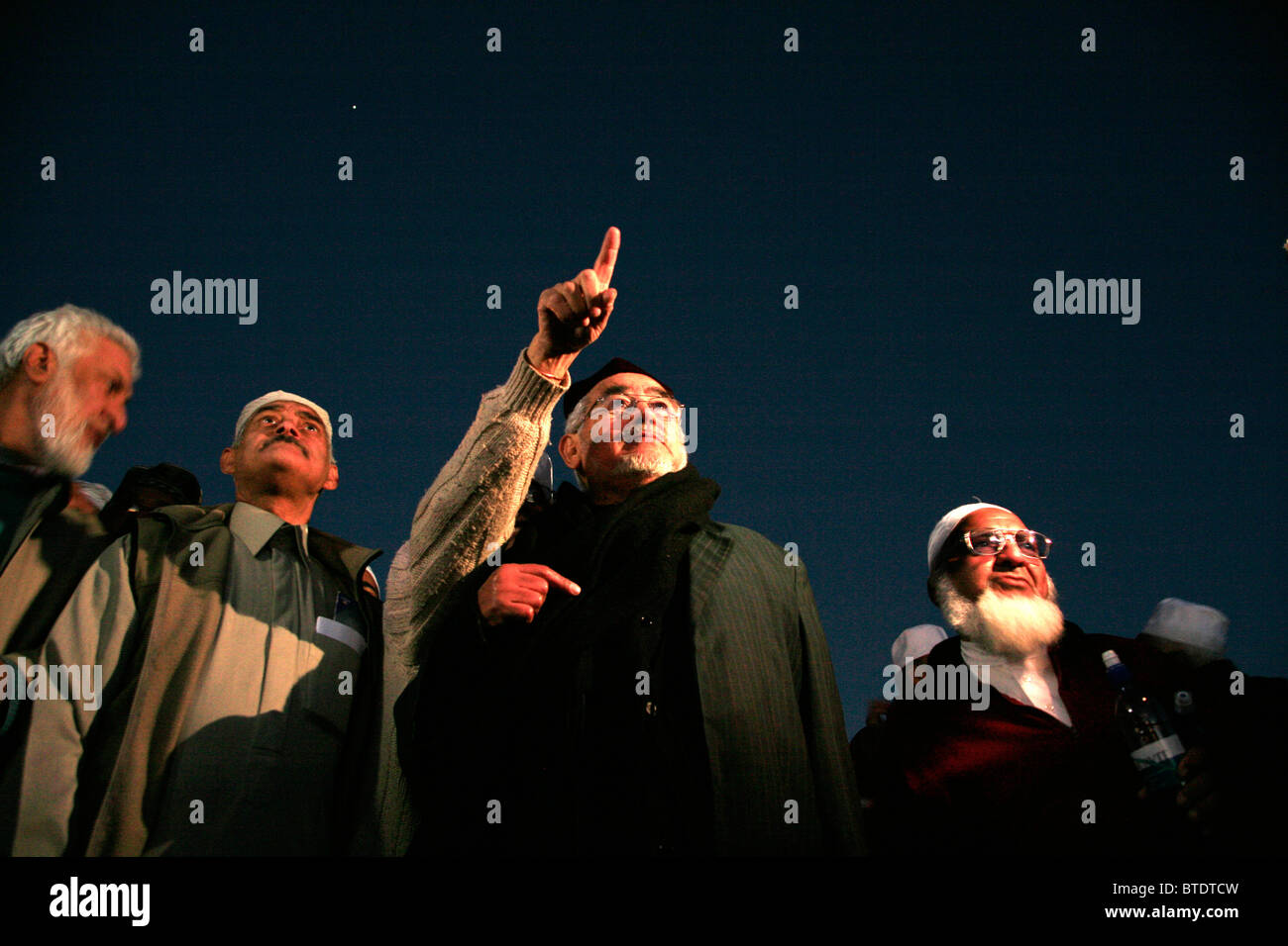 Elderly Muslim men looking and pointing for the first sighting of the moon, signifying the end of the Ramadan fast - Stock Image