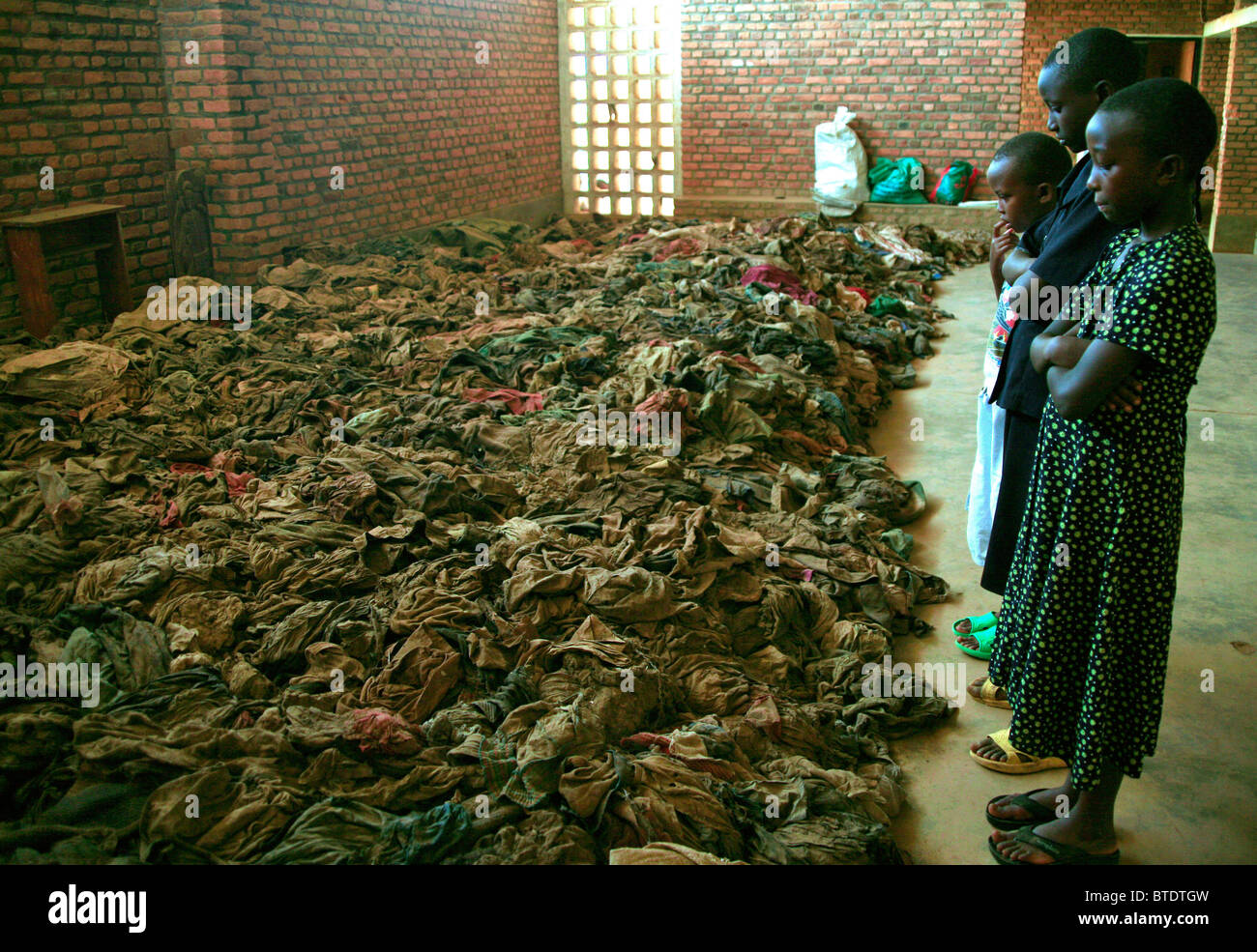 Children standing in a church in rural Rwanda and looking at remains opeople killed during the 1994 genocide - Stock Image