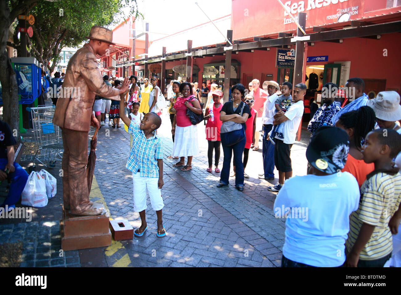 Tourists at the Victoria and Alfred Waterfront watching a street mime artist - Stock Image