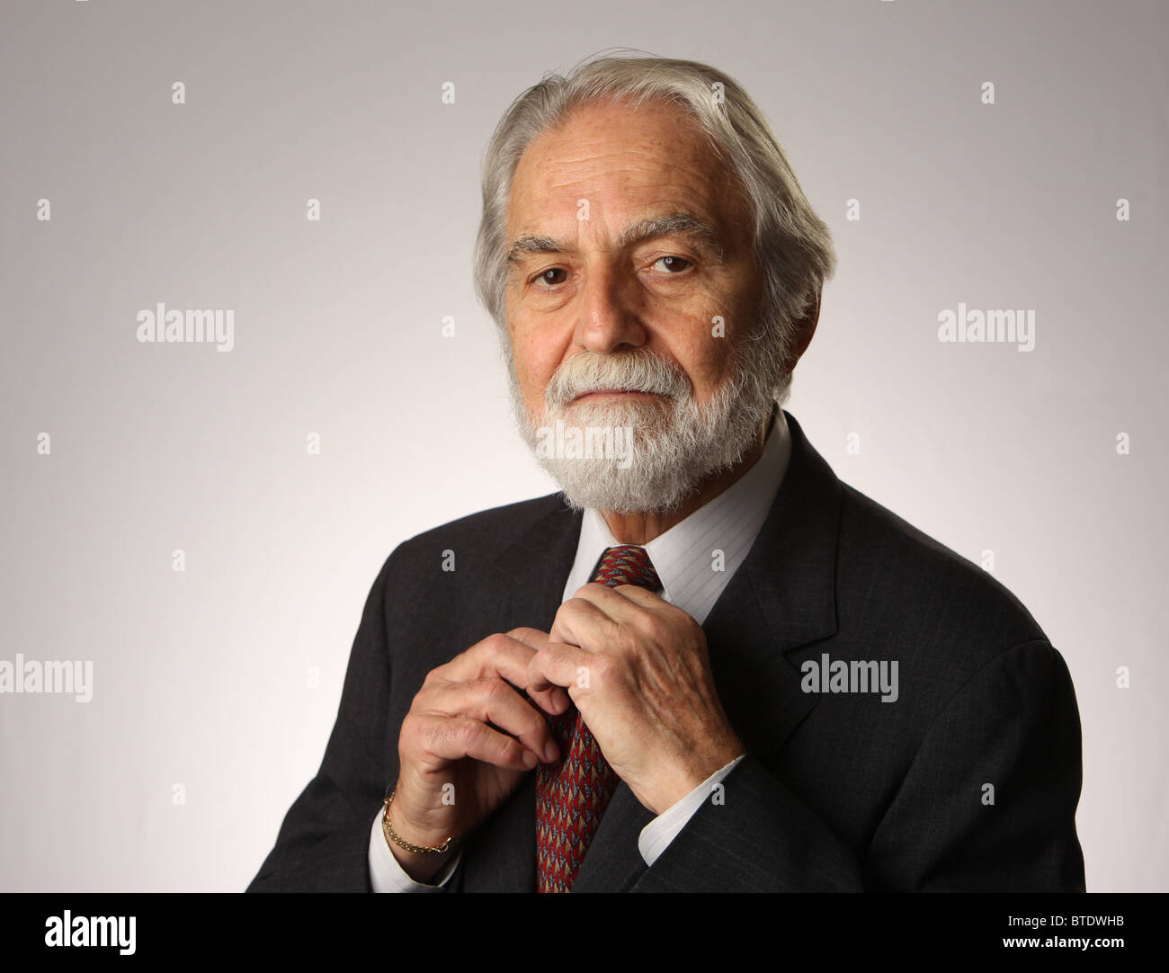 Portrait of bearded and grey haired senior businessman adjusting his tie, studio shot, white, grey background, October - Stock Image