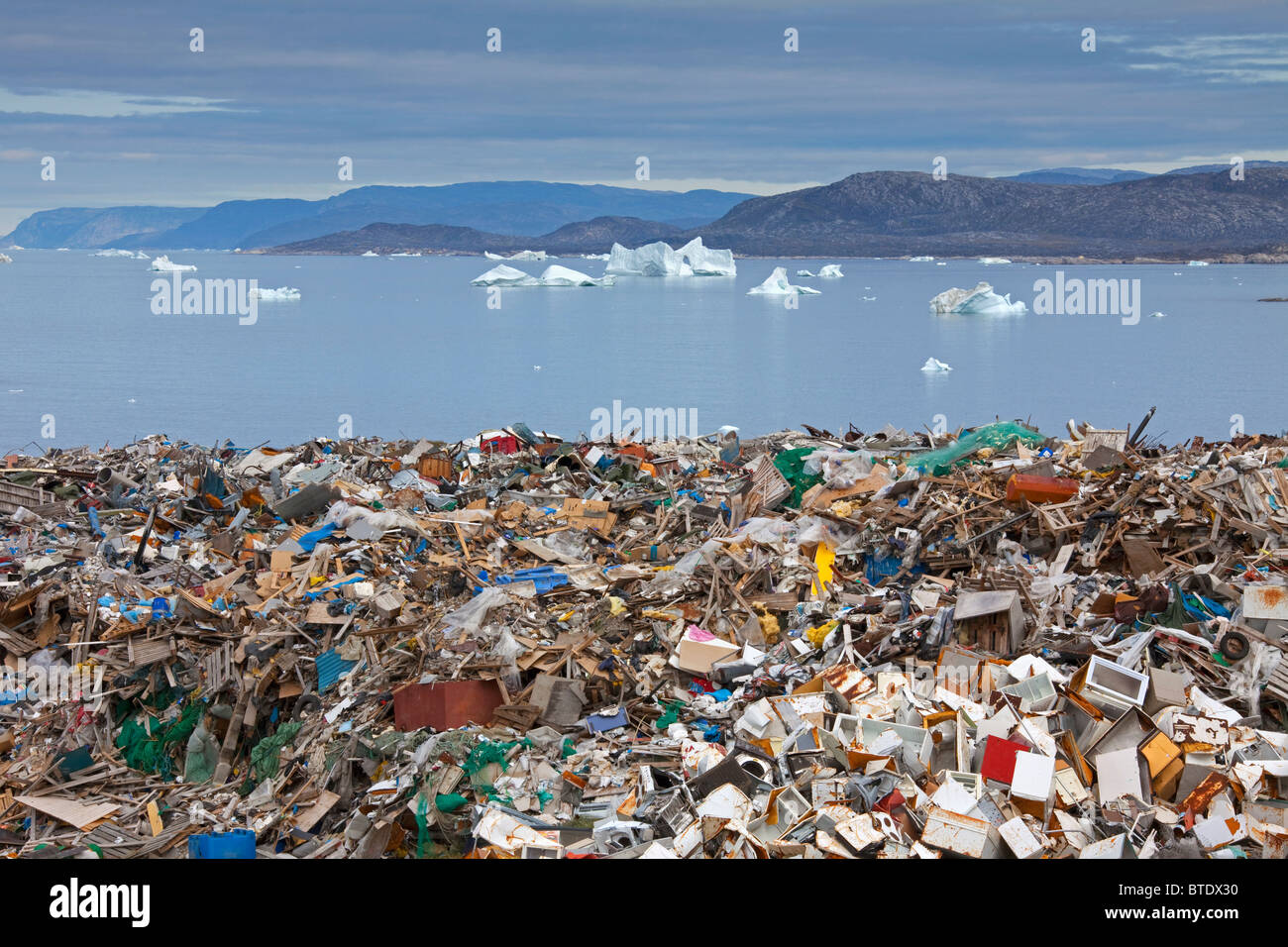 Rubbish at garbage dump and icebergs at Ilulissat / Jakobshavn, Disko-Bay, Greenland - Stock Image