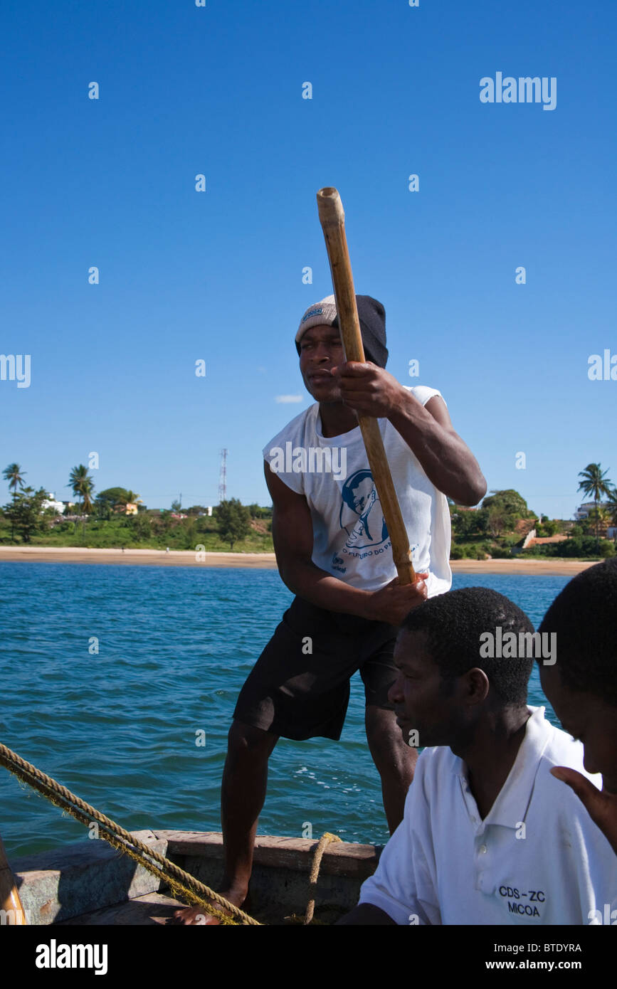 Dhow boatmen poling their boat into shore - Stock Image