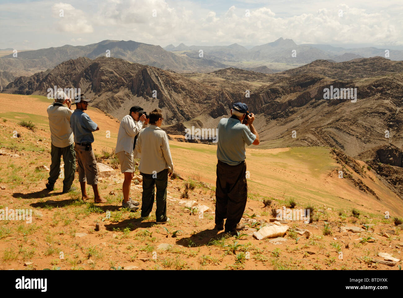 Tourists looking at Kunene River valley, Serra Cafema Mountains and Angola in background - Stock Image