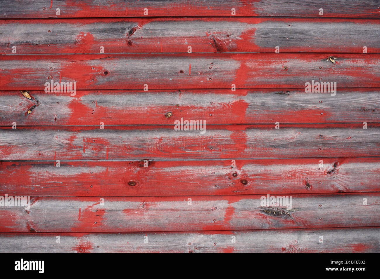 Some old wood siding with splotches of red paint. - Stock Image