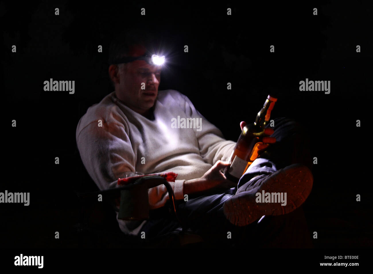 Man sitting with a headlamp on looking with  awe at a bottle of very expensive whiskey - Stock Image