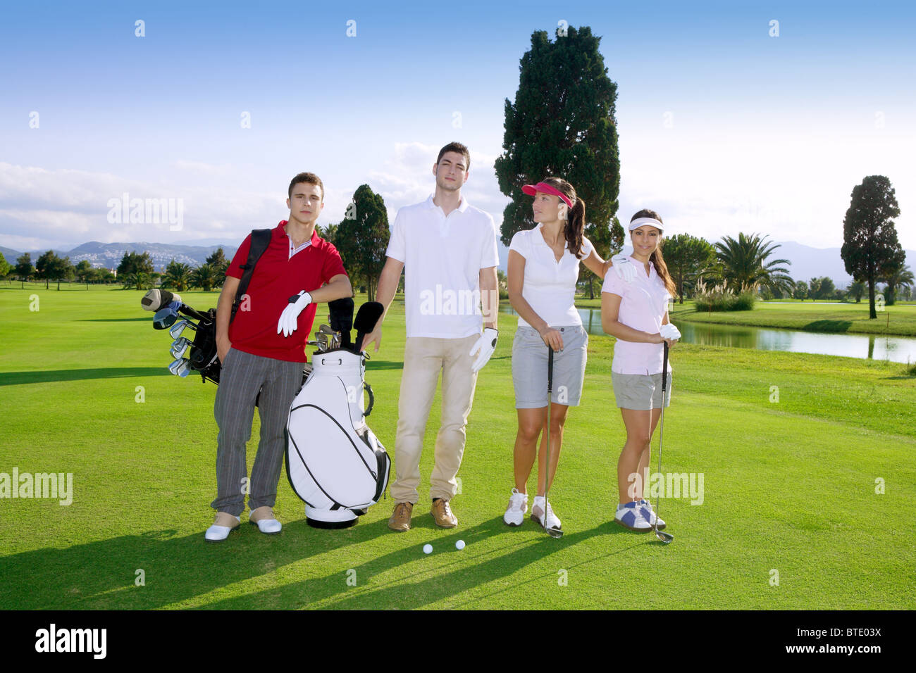Golf course people group young players team grass field - Stock Image