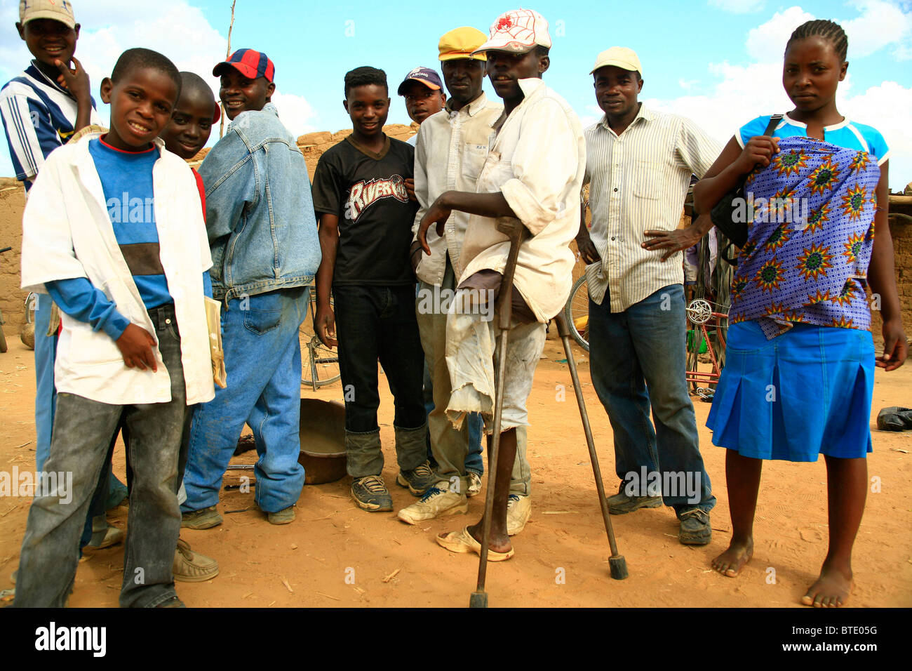 Group of people at the roadside in southern Angola, including one man with crutches who had a leg blown off by a - Stock Image