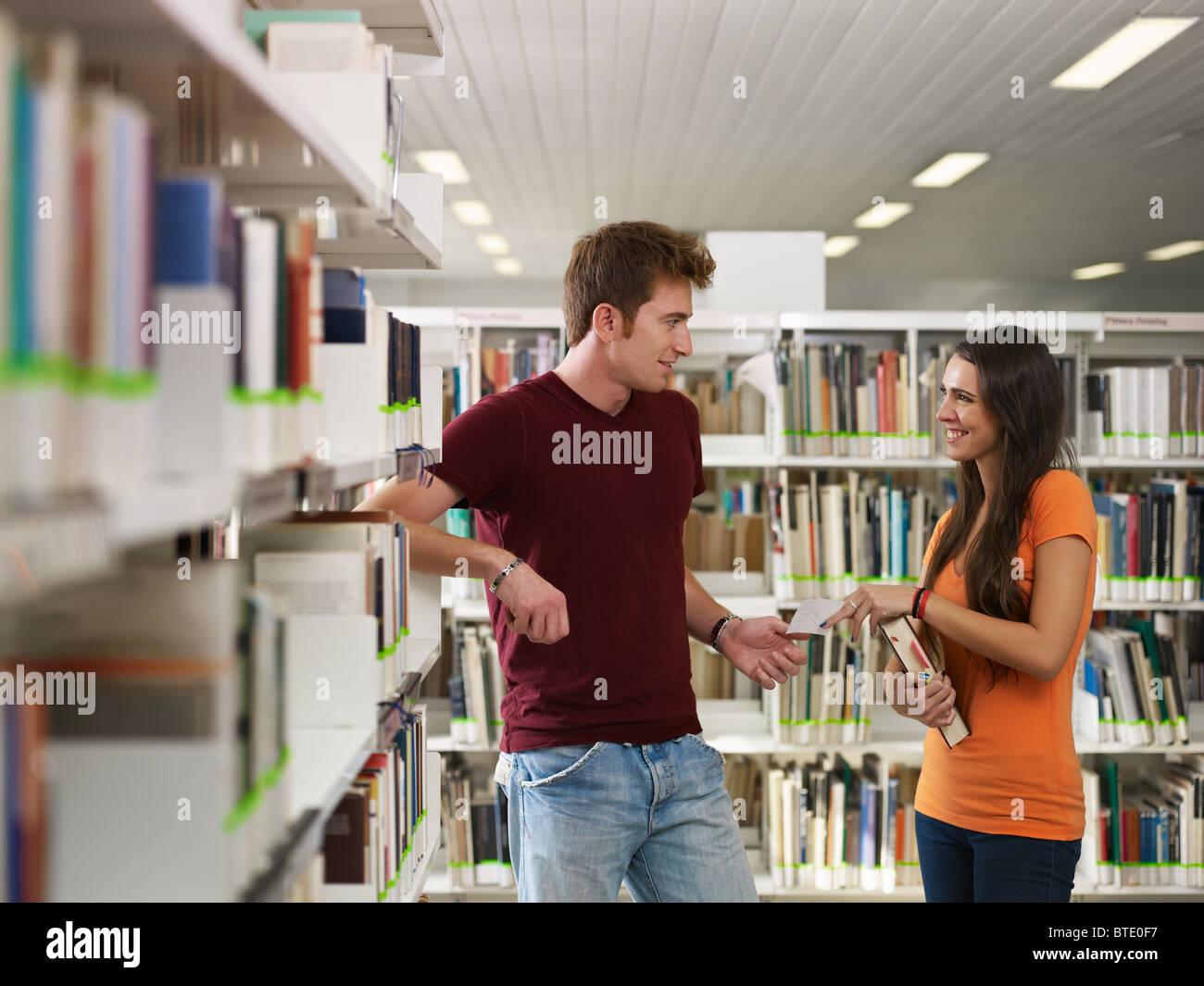 female college student giving phone number to her mate. Horizontal shape, side view, copy space - Stock Image