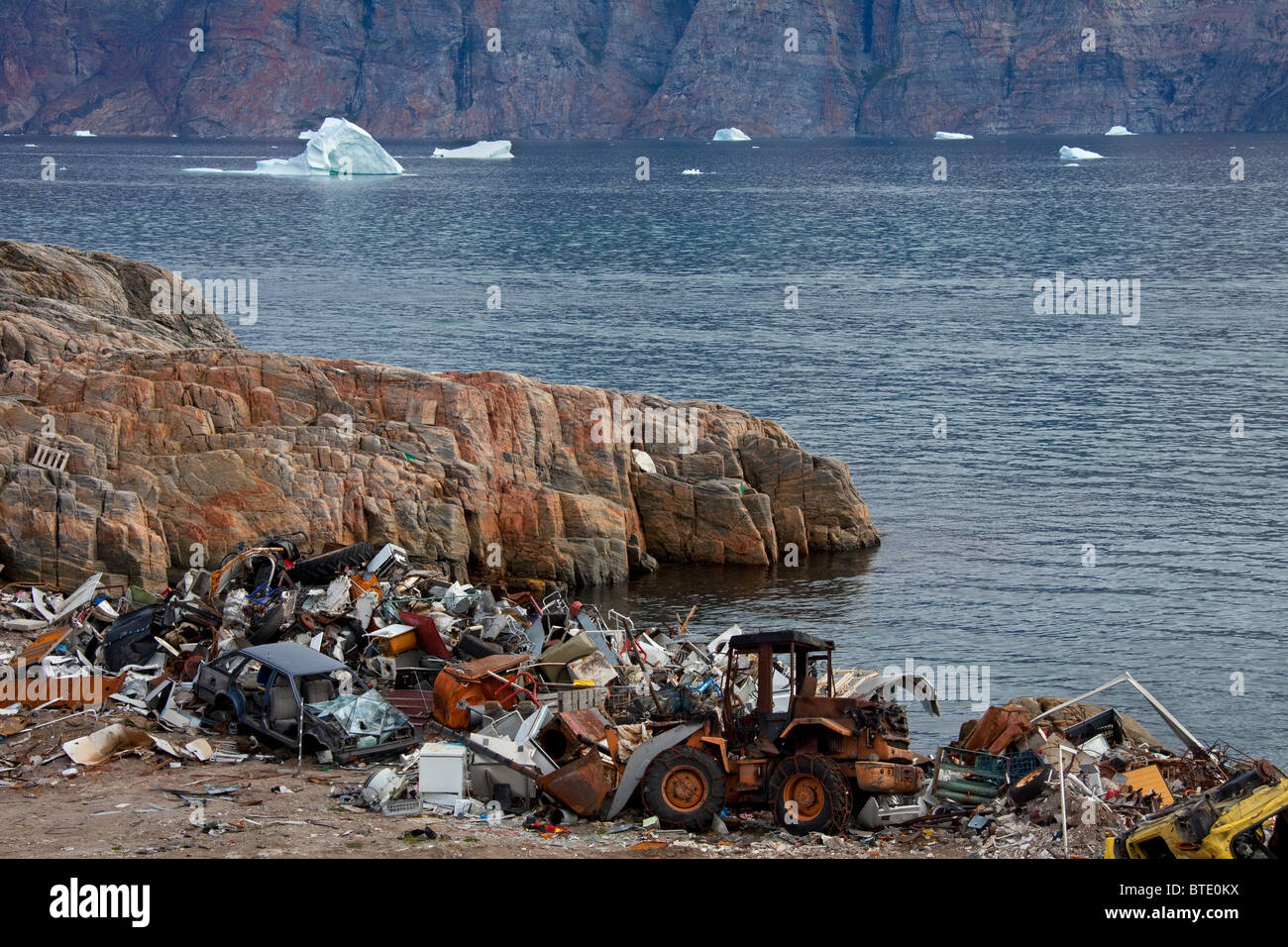 Rubbish at garbage dump and icebergs at the fishing village Uummannaq, Greenland - Stock Image