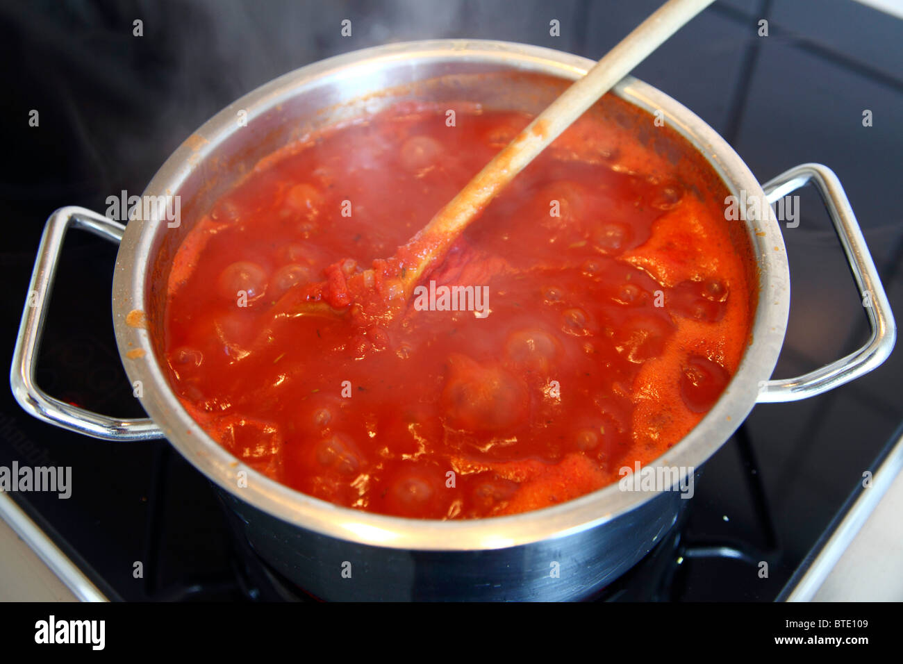 Cooking pot with boiling tomato sauce on an electric oven. - Stock Image