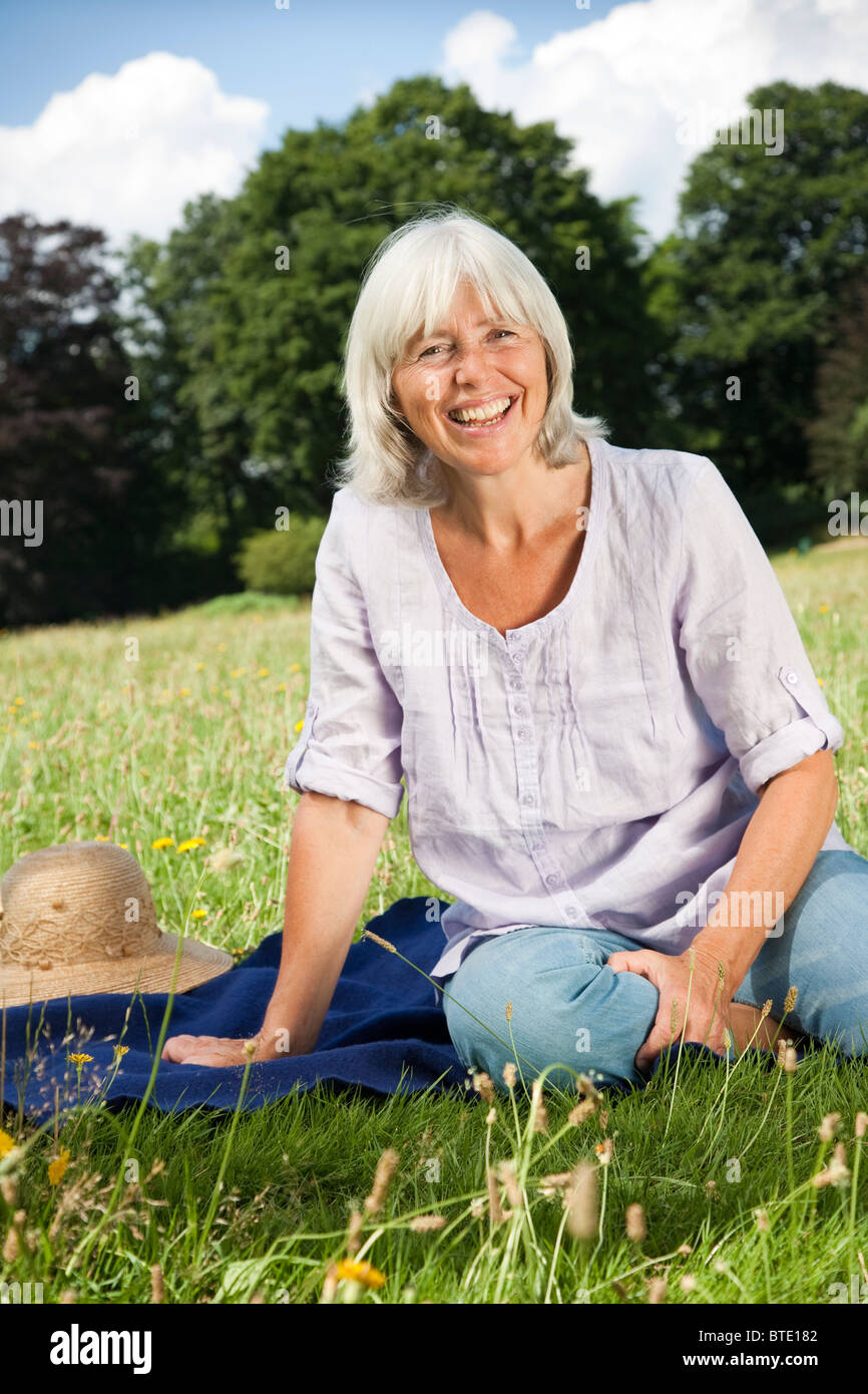 Laughing woman sitting in the grass - Stock Image