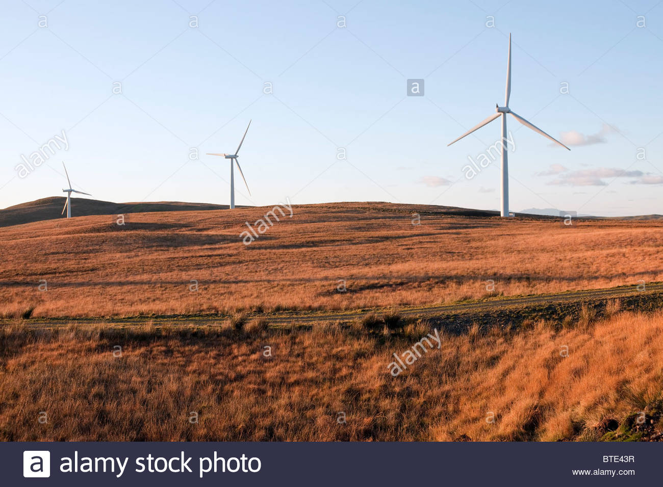 Line of wind turbines on moorland at Hadyard Hill, Ayrshire, Scotland. The Isle of Arran in the distance - Stock Image