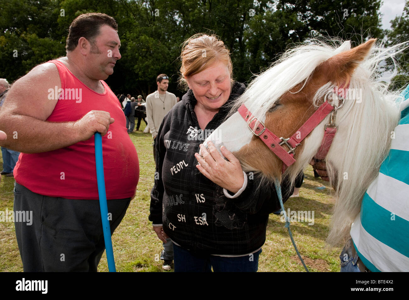 Horse dealer with a very large stomach looks admiringly at a woman holding his horse's head at Priddy Sheep - Stock Image