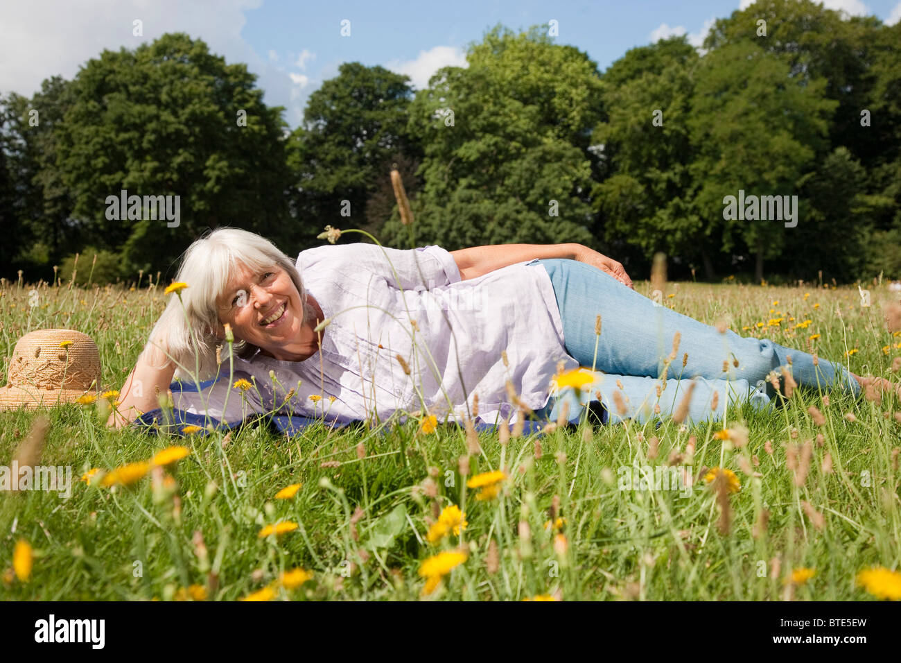 Woman lying in the grass - Stock Image
