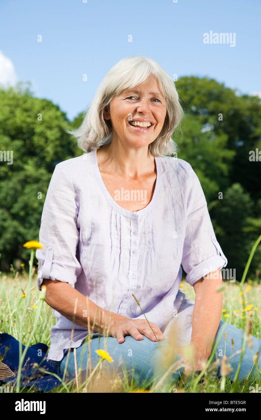 Elderly lady sitting in the grass - Stock Image