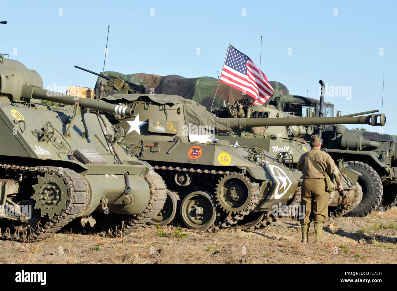 USA Military tanks and truck with soldier in a WWII uniform standing