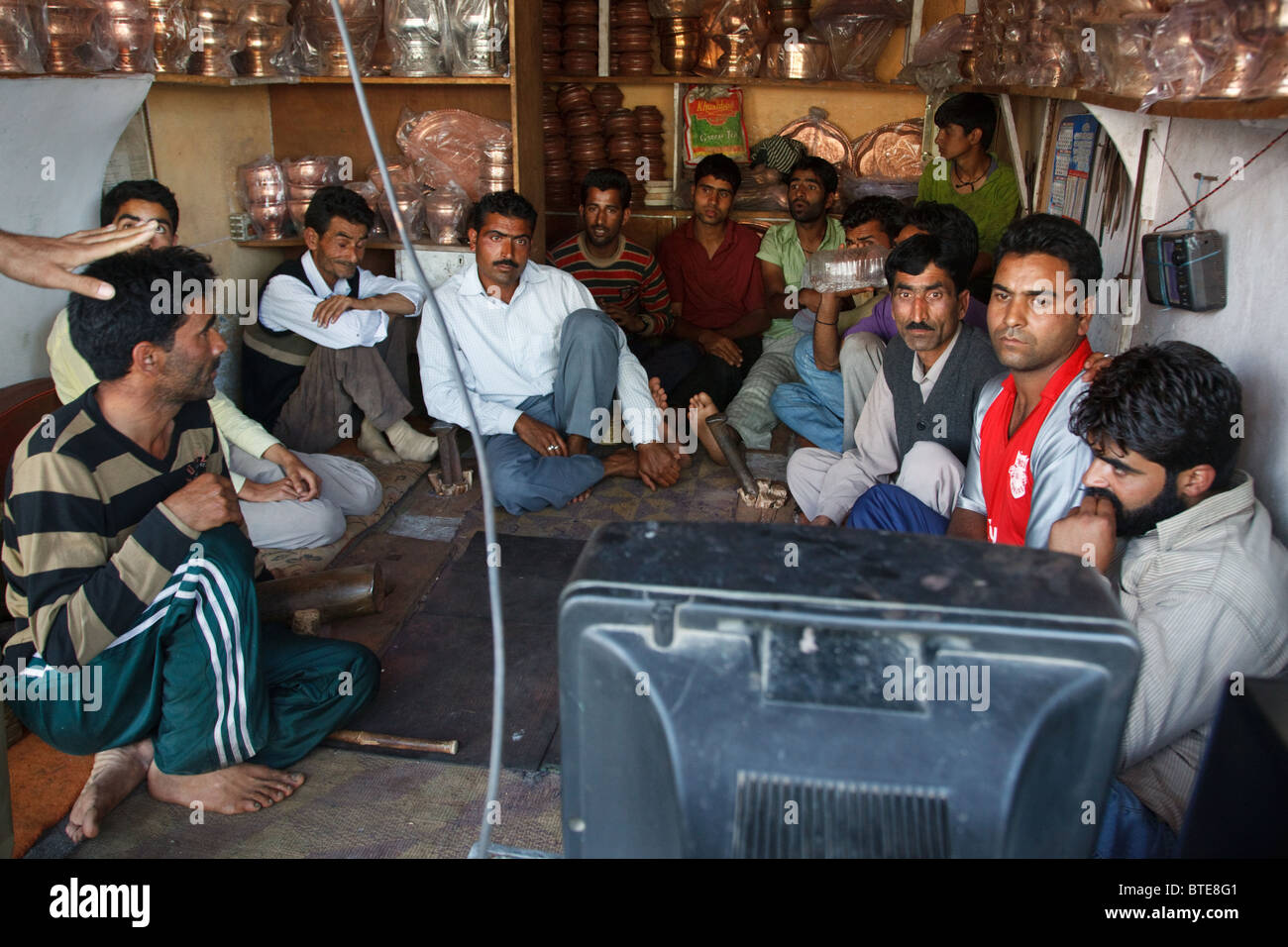 Men watch an India-Pakistan cricket match on a TV in a small shop in Srinagar, Jammu and Kashmir, India - Stock Image