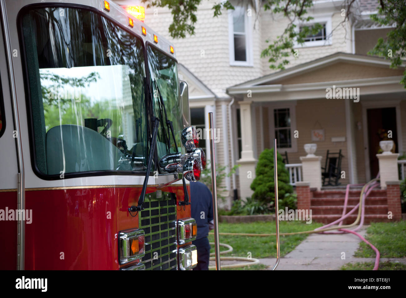 Close-up of a shiny red fire engine in front of a house with hoses. - Stock Image