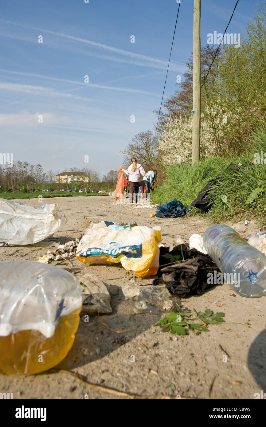Trash dumped on dirt road, volunteers in background cleaning up - Stock Image