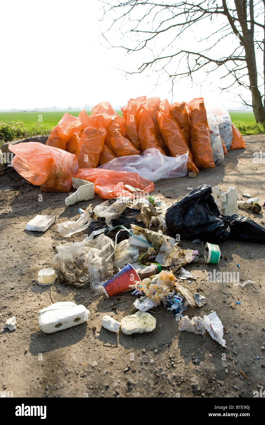 Trash dumped outdoors, full bags of trash in background result of cleanup effort - Stock Image