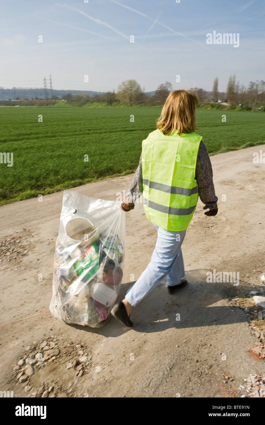 Volunteer carrying garbage full of trash outdoors - Stock Image