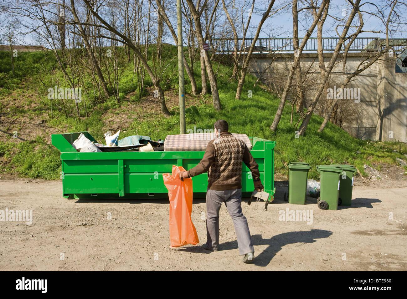 Man taking garbage to dumpster - Stock Image