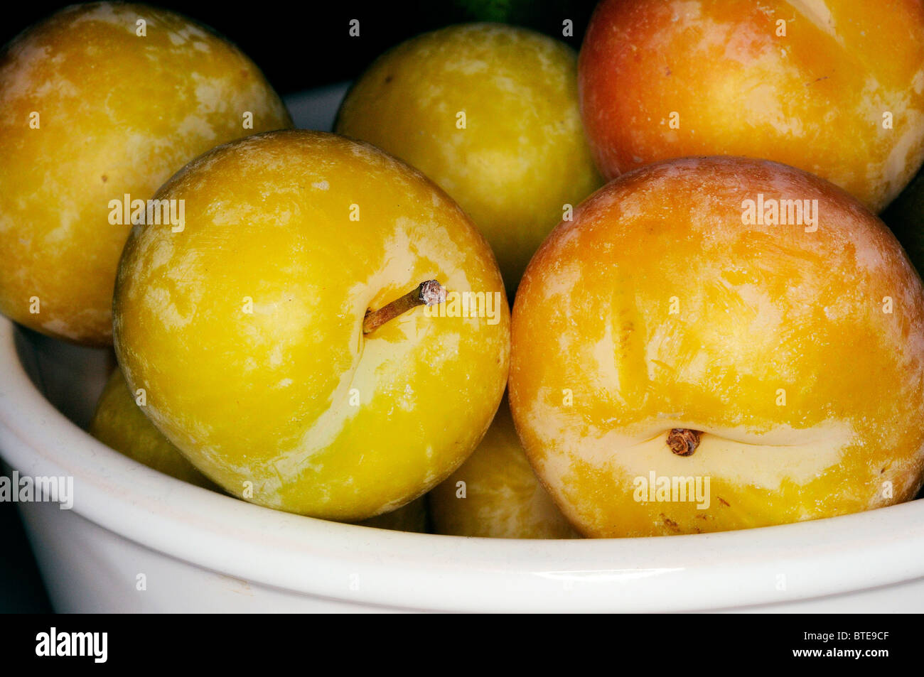Yellow plums in bowl - Stock Image