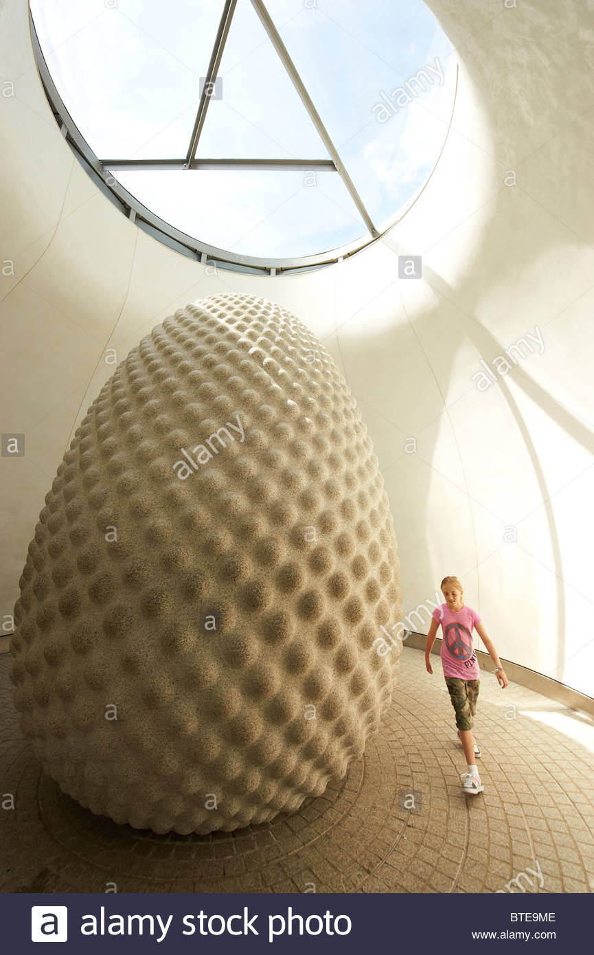 A young girl at The Core Building with a sculpture of a giant seed at The Eden Project  near St Austell - Stock Image