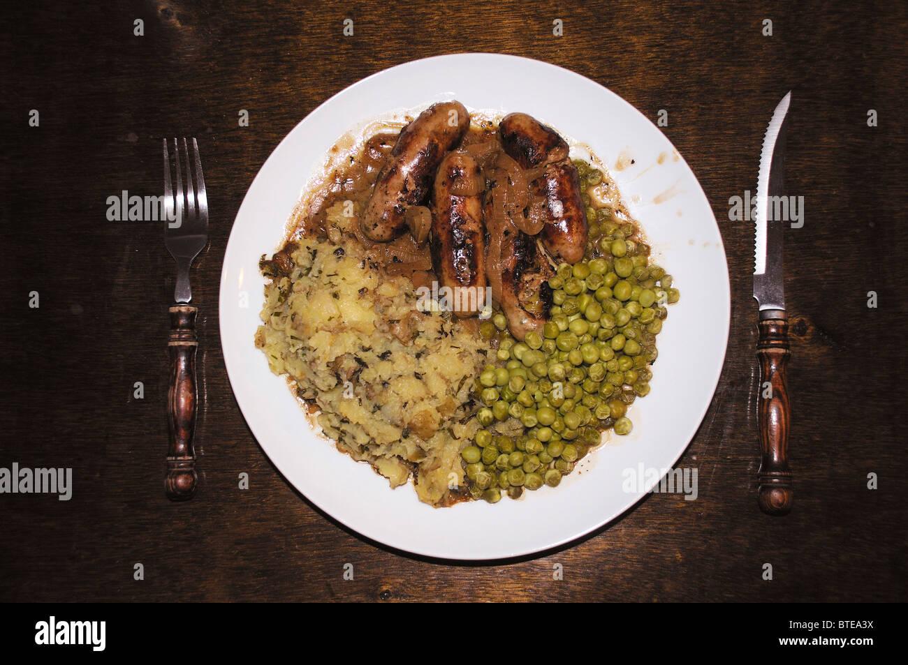 Bangers and mash, a dish consisting of sausage, mashed potatoes and peas Stock Photo