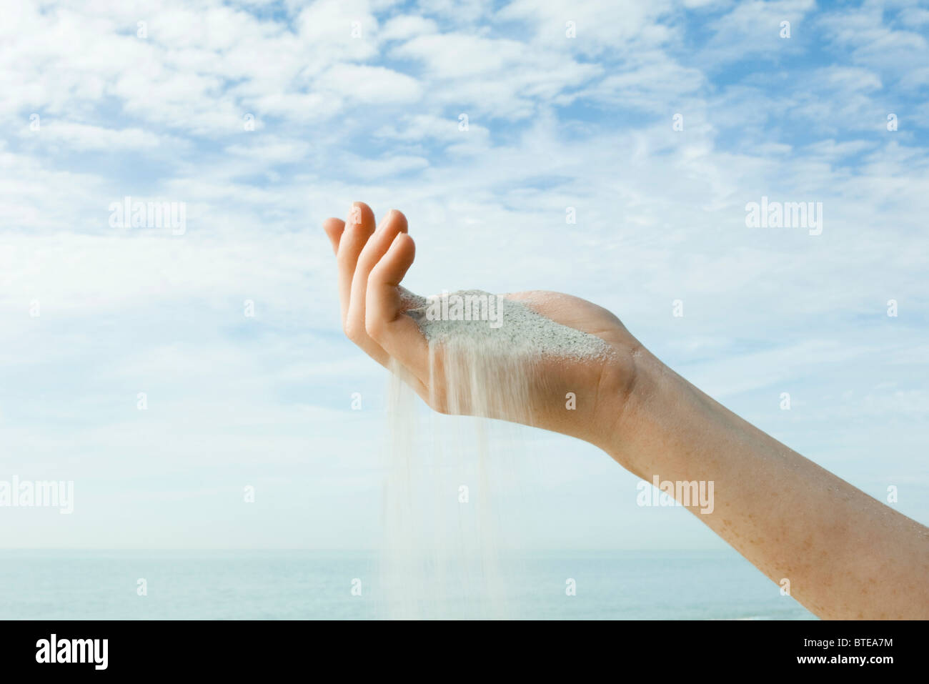 Sand spilling from cupped hand Stock Photo